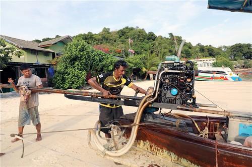 皮皮岛的沙滩上,一位船夫正在同伴的帮助下修理发动机。虽然船体老化,但是船夫依然每天带领大量游客出海游玩。本报记者赵益普摄.jpg