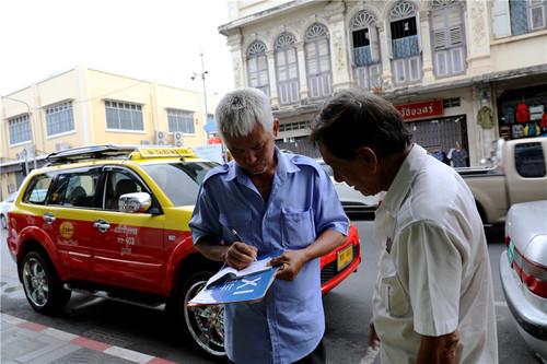 在普吉市区,一位出租车司机正在教另一位出租车司机写英文收据。普吉岛的出租车几乎都不打表,如有乘客需要发票,均由司机手写一张收据。本报记者赵益普摄.jpg